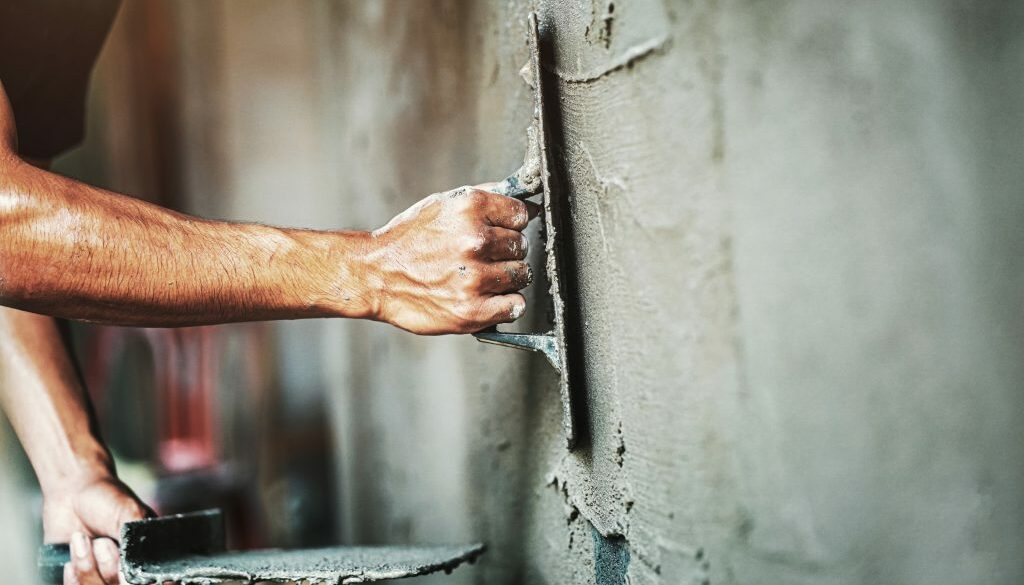 closeup hand of worker plastering cement at wall for building ho