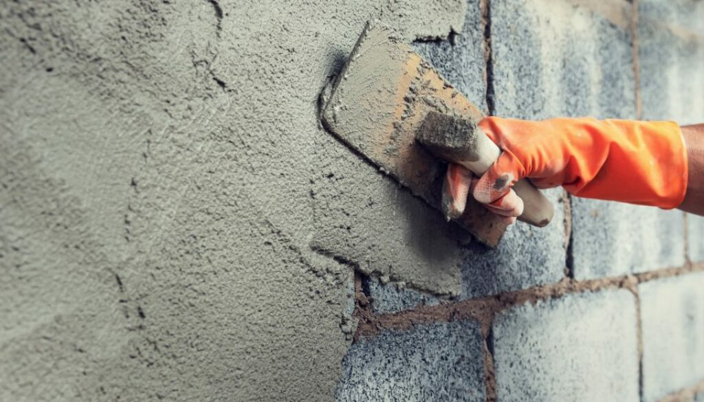 close up hand worker plastering cement on wall for building hous