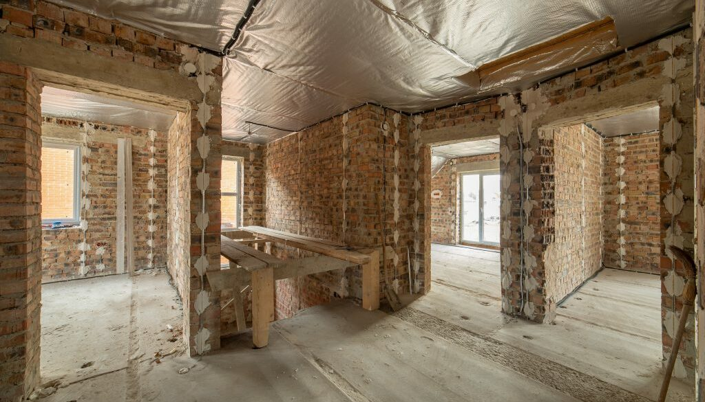 Interior of unfinished brick house with concrete floor and bare